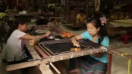 Artisans work on a tapestry at the Aung Nan Myanmar Handicraft workshop in Mandalay Myanmar on Sunday June 11 CU an artisan works on a tapestry