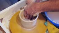 Handen van de kunstenaar een kom op een aardewerk wiel vormgeven