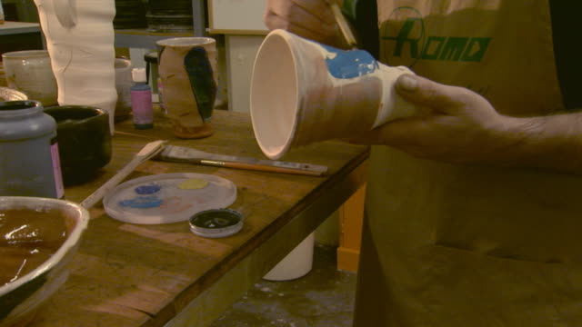 Artist is working on painting a finished clay cup