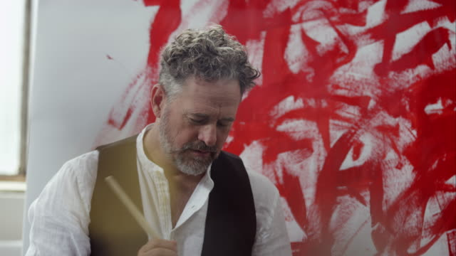 Artist painting with red color on canvas