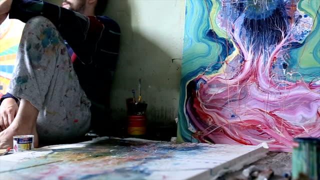 Kunstenaar zittend op de vloer