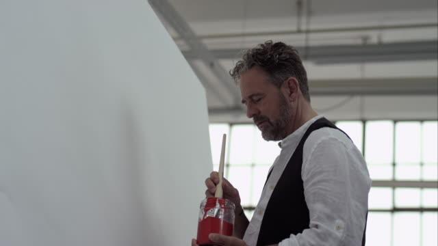 Artist starts painting with red color on canvas