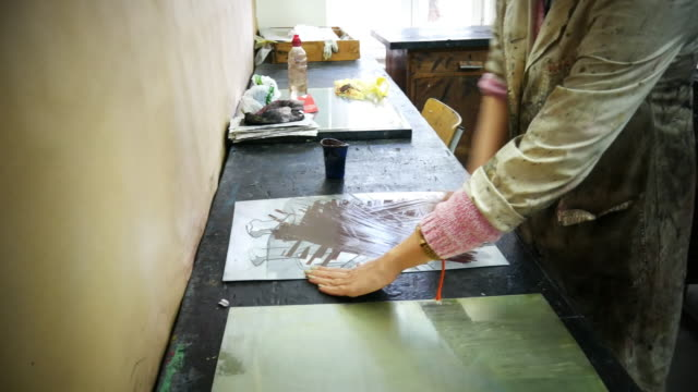 Artist working applying dark ink on mould surface