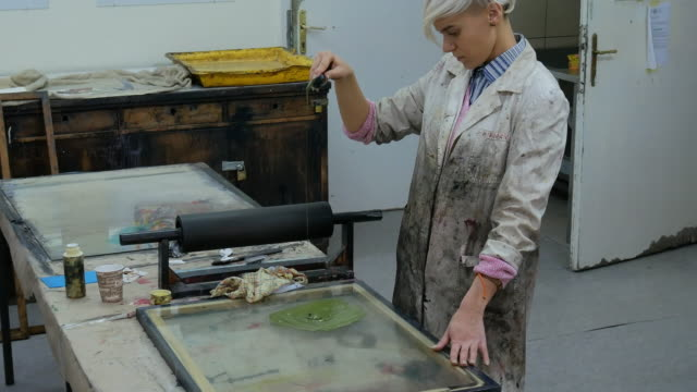 Artist working in her workshop with intaglio printing