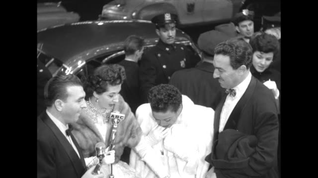 As cars behind them discharge passengers and move along ABC hosts interview Hazel Scott and husband Adam Clayton Powell Jr Scott looks down /...