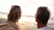 POV as couple look out to sea, from tidal flat
