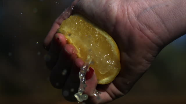 CU SLO MO As squeeze half of lemon Juice runs out
