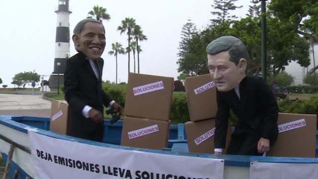 As talks to curb global warming deadlock on the last official day in Lima activists dressed as large dolls resembling world leaders board a boat from...