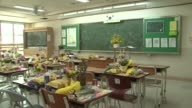 As the one year anniversary of the sinking of the Sewol Ferry approaches an empty classroom in Danwon high school is filled with flowers and...