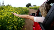 POV as woman extends arm out of car window, rural track