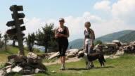PAN as women walk along path with dog, check signpost