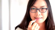 HD: Asai woman make up lipstick in mouth.