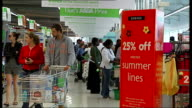 London INT Interior general views Asda supermarket featuring signs hanging from ceiling shoppers with trolleys browsing food queuing at checkouts /...