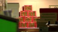 Asda supermarket Christmas preparations ENGLAND Asda staff member stocking shelves/ 'Christmas' sign hanging from shelves/ staff member stocking...