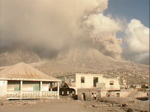 Ash clouds billow from the Soufriere Hills volcano above the ruined town of Plymouth Montserrat 1998