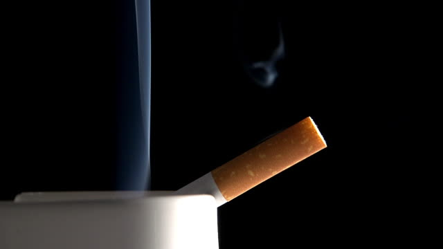 Ashtray with Smoking Cigarette against Black Background, Real Time