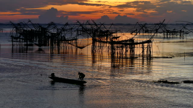 Asia Fishermen in the early morning golden light casting sow net fish