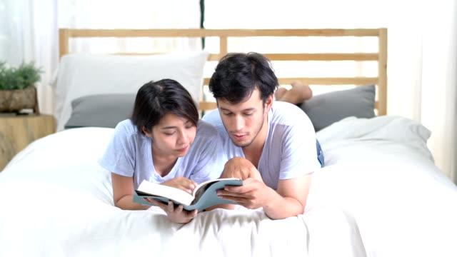 Azië jong koppel een boek lezen op bed thuis