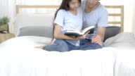 asia young couple read a book on bed at home