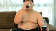 Asian fat man drinking cola in home