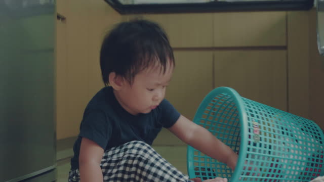 Asian baby boy learning to fold laundry at home