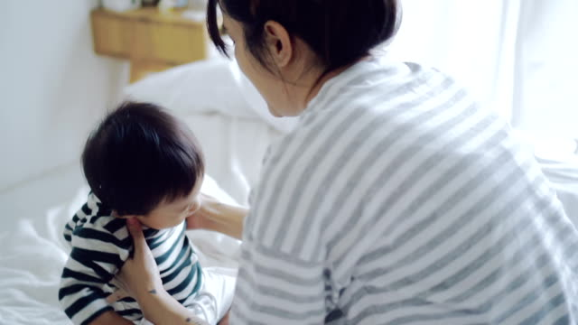 Asian Baby (6-11 months) Boy Learning To Walk With Mother.