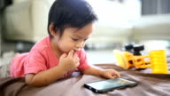 Asian baby boy looking at mobile phone screen.