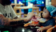 Asian baby (6-11 months) eating baby food in restaurant.