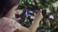 Asian Baby Girl Decorating Christmas Tree With Ornaments