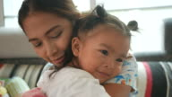 Asian baby girl embracing with mother