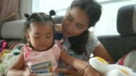 Aziatische baby spelen en lezen boek met moeder