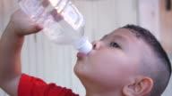 Asian boy drink water from bottle