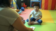 4K: Asian boy learning new words and math by looking at flash cards showing by mom
