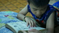 Asian boy reading book in bedroom