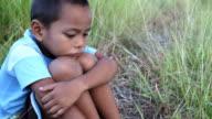 Asian boy sitting in field