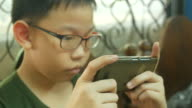 Asian boy using digital game with smart phone
