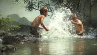 HD: Asian boys having fun playing in the river with splashing water together
