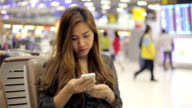 Asian business woman on smart phone at airport