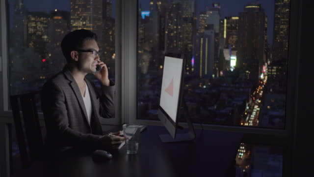 Asian Businessman Sitting in Office with Cityscape Background. Using Mobile Phone and Desktop Computer.