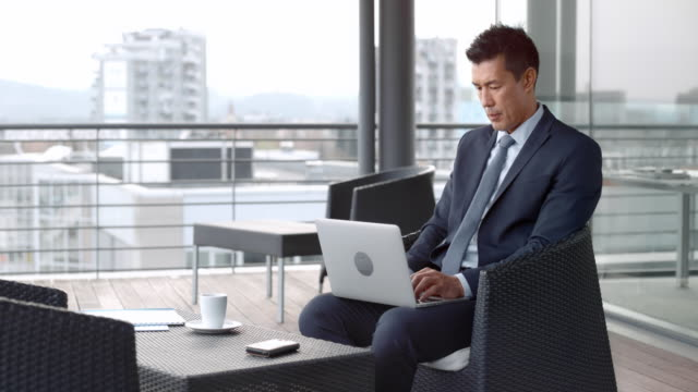 Asian businessman sitting in the lounge and working on the laptop