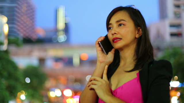 Asian businesswoman talking with mobile with night scene