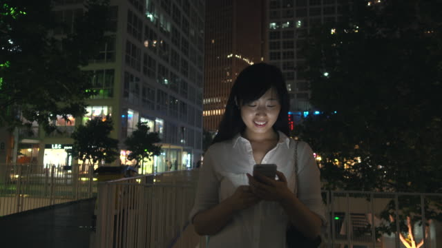 Asian businesswoman using smart phone at city night