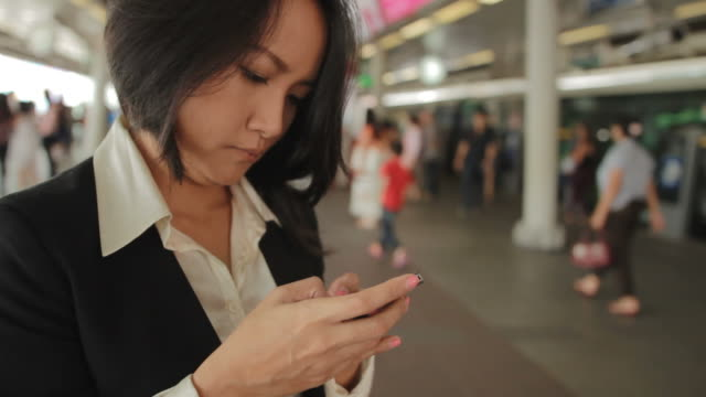 Asian businesswoman working with smartphone at train station platform