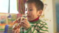 Asian children and preschool teacher eating pizza in classroom
