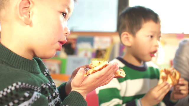 Asiatische Kinder und Kinder, Lehrer im Klassenzimmer Essen pizza