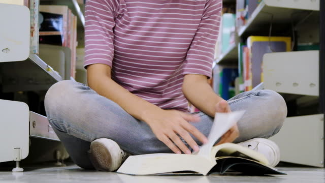 Asian college student sitting on floor in library, reading book.
