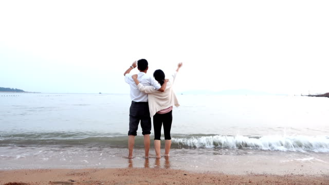 Asian couple standing at sea beach