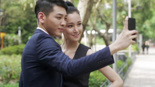 Asian couple taking selfies.