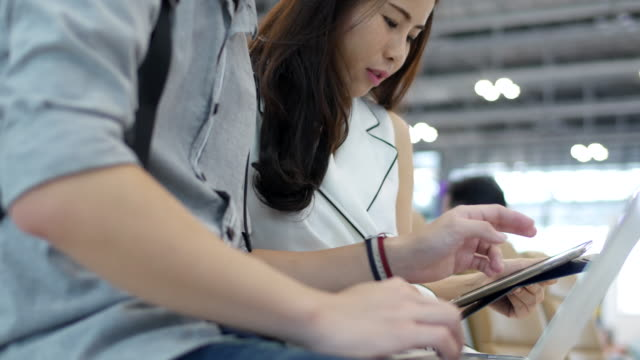 Asian cute women play tablet at the airport.