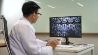 Asiatischen Arzt arbeitet an seinem Schreibtisch in Krankenhäusern